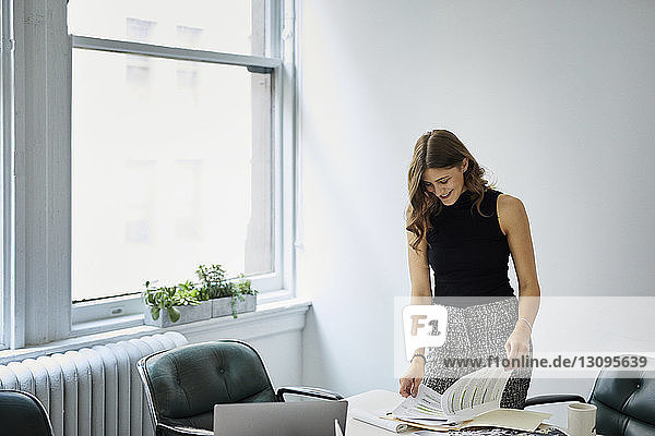 Smiling businesswoman examining documents while standing at conference table in office