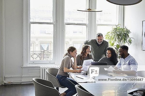 Lächelnde Geschäftsleute diskutieren über Laptop-Computer im Konferenzraum des Kreativbüros