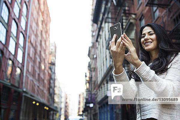 Glückliche junge Frau fotografiert durch Smartphone in der Stadt