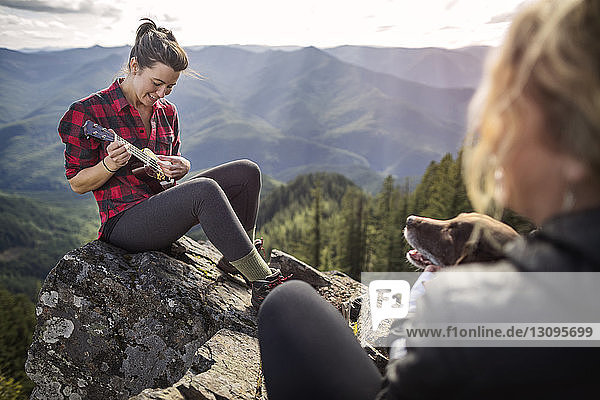 Woman playing ukelele on rock at mountain cliff