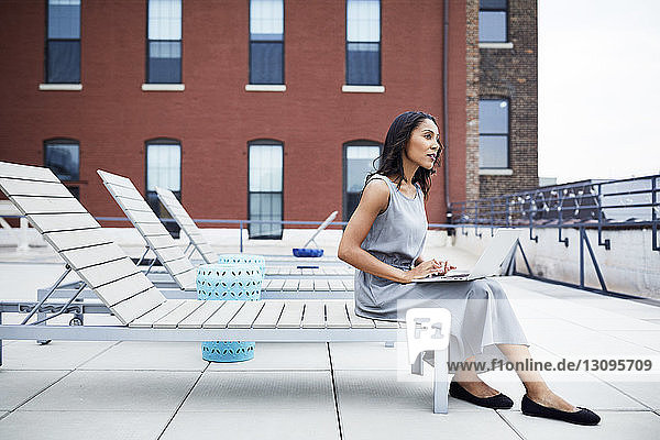 Thoughtful businesswoman with laptop computer sitting on lounge chair at building terrace