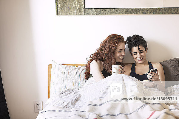 Lesbian showing mobile phone to girlfriend while sitting on bed