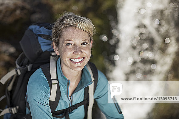 Portrait of cheerful female hiker carrying backpack