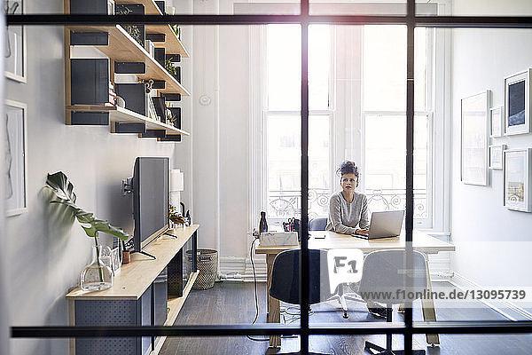 Geschäftsfrau mit Laptop-Computer am Schreibtisch durch Fenster im Büro gesehen