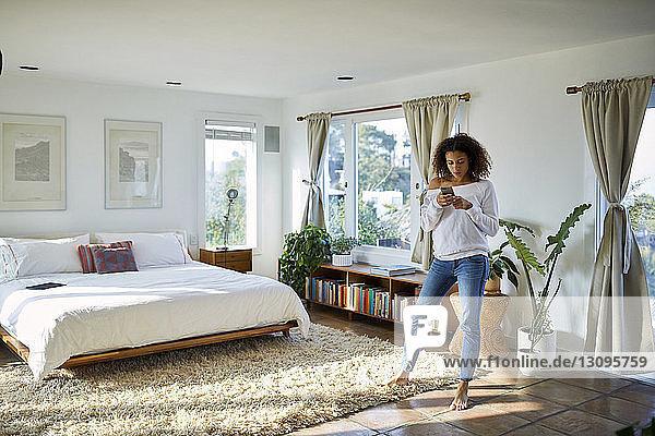 Frau benutzt Mobiltelefon  während sie zu Hause im Schlafzimmer steht