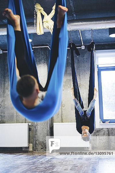 Mann und Yogalehrerin hängen während des Trainings im Fitnessstudio an Hängematten