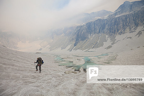 Rear view of hiker walking on glacier against sky