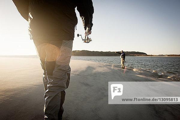 Men preparing for fishing at beach during sunset