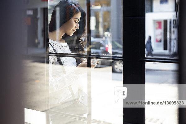 Junge Frau mit Smartphone durch Glaswand gesehen
