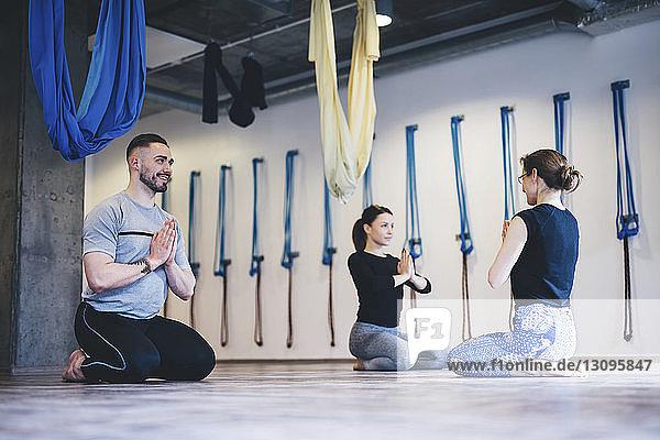 Freunde und Lehrer mit gefalteten Händen beim gemeinsamen Yoga-Training in der Turnhalle