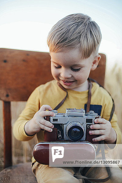 Happy boy with vintage camera sitting on chair amidst field