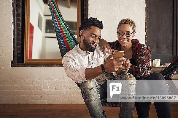 Glückliches junges Paar benutzt Smartphone  während es zu Hause auf der Hängematte sitzt