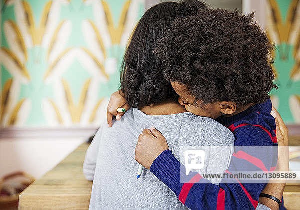 Loving boy embracing mother while holding crayons at home