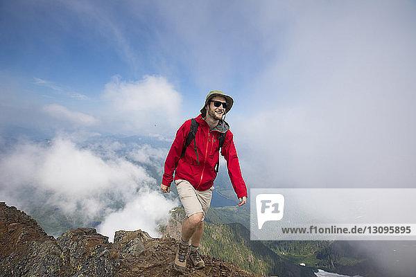 Glücklicher Wanderer steht auf Berg gegen wolkigen Himmel