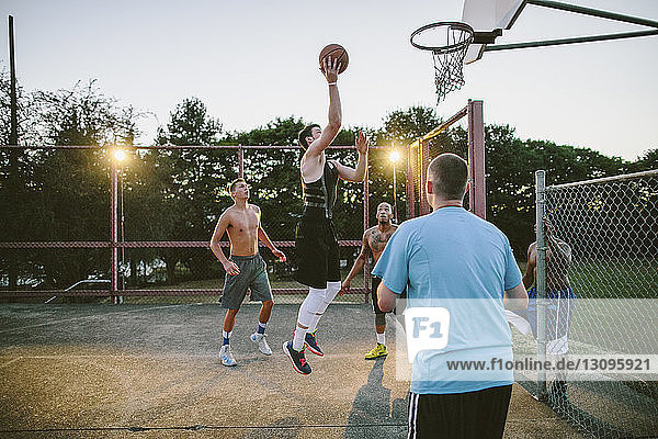 Friends looking at man dunking while practicing basketball in court during sunset