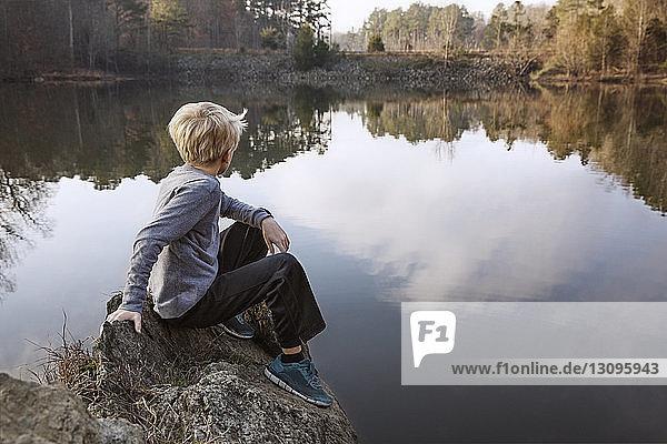 Boy sitting on rock by lake
