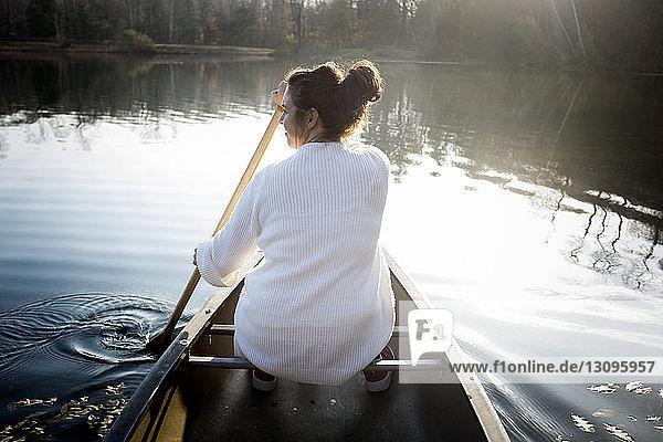 Rückansicht einer Frau  die in einem Boot auf einem See im Wald sitzt