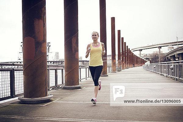 Frau läuft auf Brücke