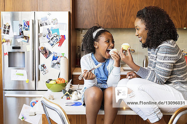 Happy mother and daughter looking at each other while eating cupcakes on kitchen island