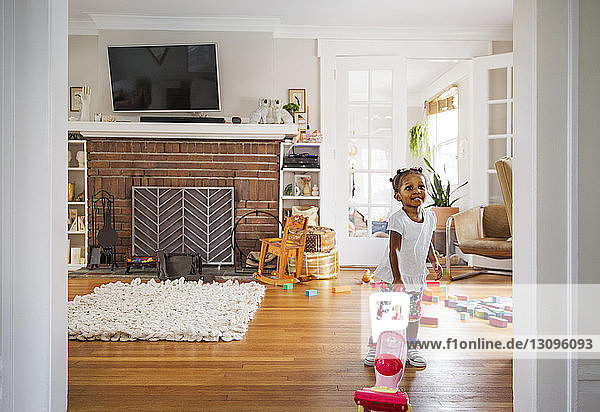 Cute girl looking away while pulling toy at home