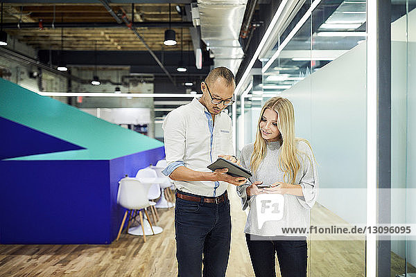 Young business people discussing over tablet computer while standing at corridor