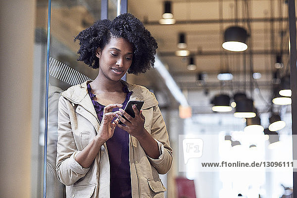 Businesswoman using smart phone while standing at doorway in office