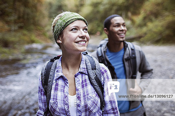 Happy woman with male hiker in forest