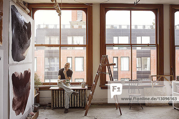 Thoughtful artist holding coffee cup while sitting by window on table at workshop