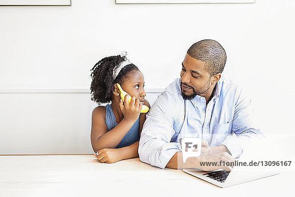 Mann hält Handy in der Hand und schaut die Tochter an  während er am Tisch sitzt