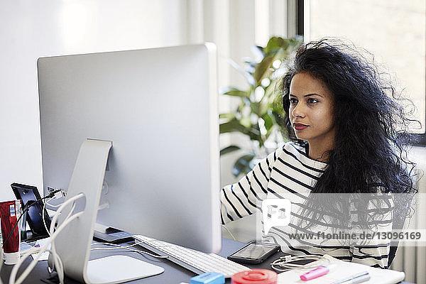 Selbstbewusste Geschäftsfrau benutzt Desktop-Computer bei der Arbeit im Büro