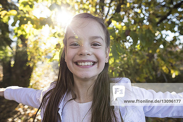 Close-up portrait of smiling girl with arms outstretched standing at park