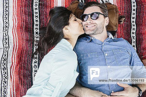 Draufsicht auf eine Freundin  die ihren Freund küsst  während sie im Park auf einer Decke liegt