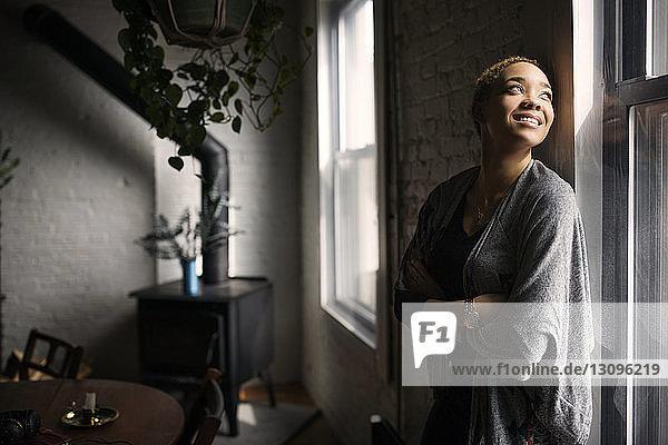 Glückliche Frau mit verschränkten Armen am Fenster stehend