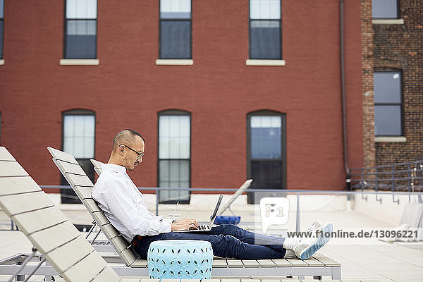 Side view of businessman using laptop while sitting on lounge chair on building terrace