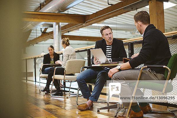 Geschäftsleute  die an Tischen im Büro arbeiten