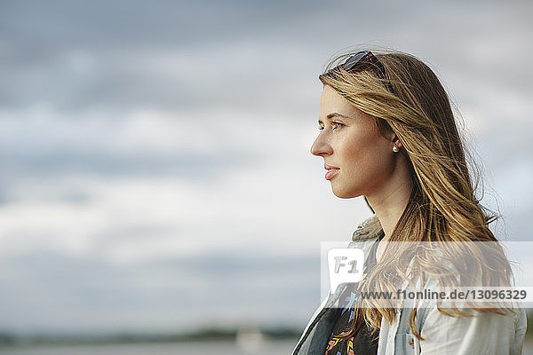 Thoughtful woman against sky