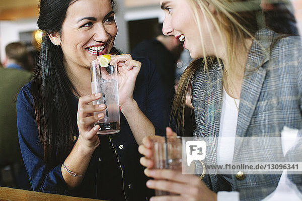 Happy friends talking while having drinks in restaurant