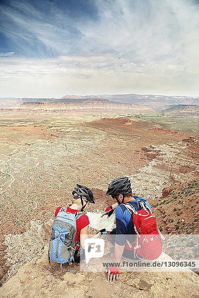 Couple reading map while sitting on cliff against sky
