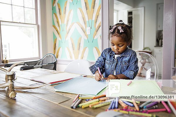 Cute girl coloring with crayon in book on table at home