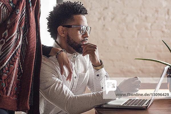 Mittendrin eine Frau  die dem Mann zu Hause am Laptop zur Seite steht