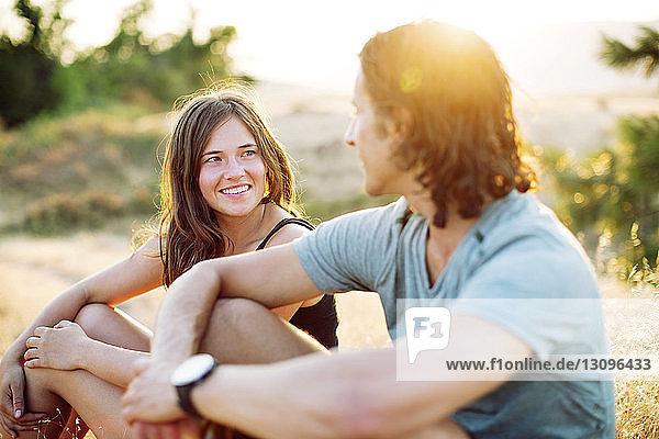 Glückliches Paar sieht sich an  während es auf dem Spielfeld sitzt