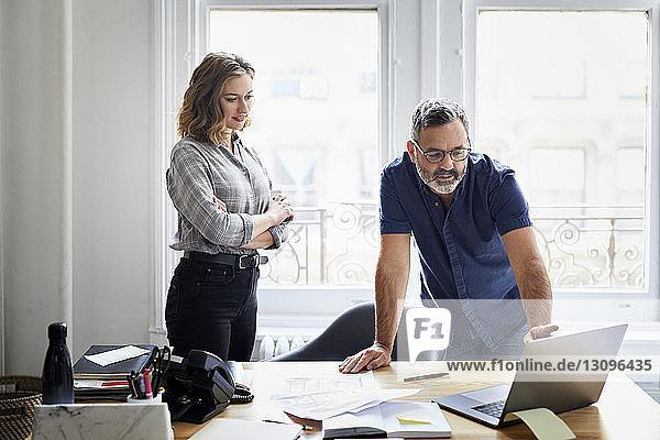 Geschäftsmann erklärt einer Kollegin im Kreativbüro am Laptop