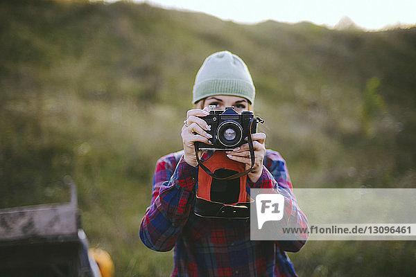 Junge Frau fotografiert mit der Kamera  während sie auf dem Feld steht