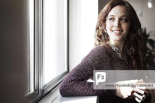 Lächelnde Geschäftsfrau schaut durch ein Fenster ins Büro