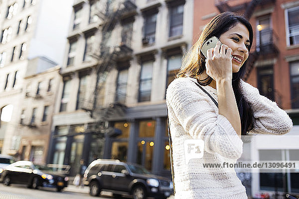Happy woman answering smart phone on city street