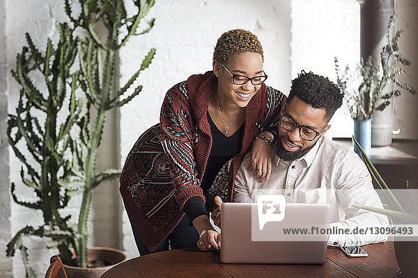 Glückliches junges Paar benutzt Laptop zu Hause