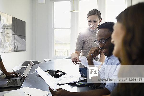 Lächelnde Geschäftsleute diskutieren Dokumente im Konferenzraum