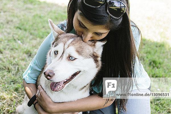 Hochwinkelaufnahme einer Frau  die einen Hund im Park umarmt