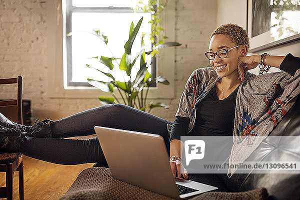 Happy woman using laptop on sofa at home