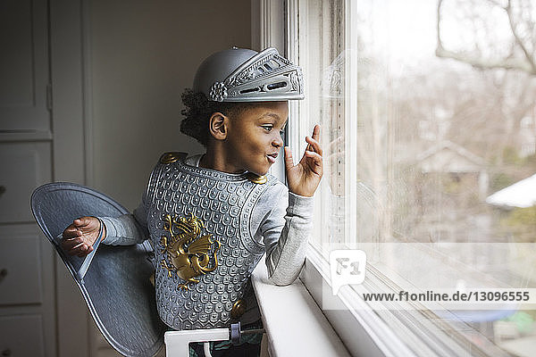 Curious boy dressed up in armor costume looking out through window at home